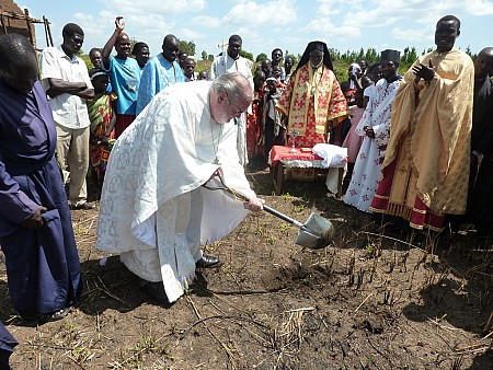 Fr. Joseph takes a turn breaking ground. Fr. George is to the right<br> in gold vestments. Metropolitan Jonah is in the background.